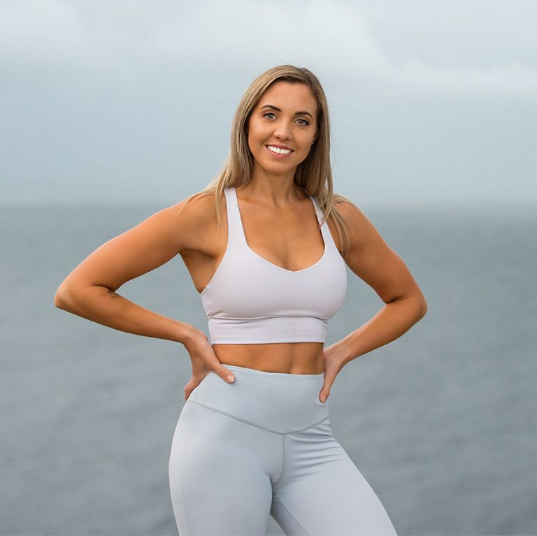 Jess Neill smiling at the beach in workout clothes