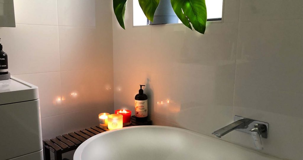 A candlelit bubble bath and white walls and a green plant under the window