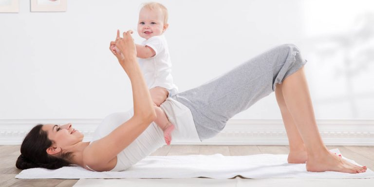 Mum and baby exercising in a white room
