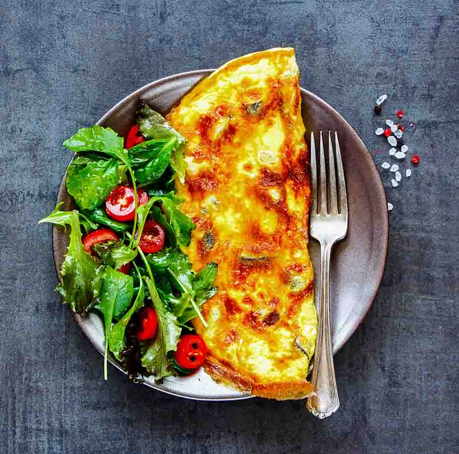 A breakfast omelette with a side salad and fork laid on a plate