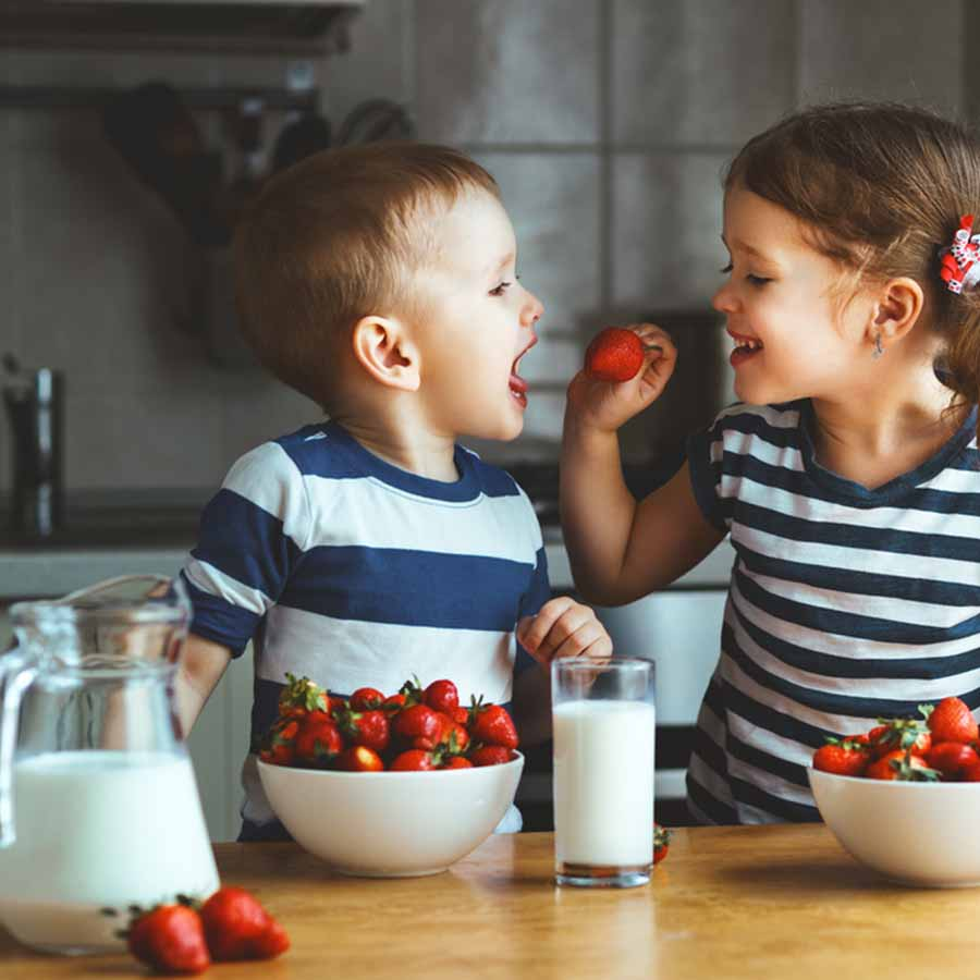 Two kids eating strawberries in the kitchen with glasses of milk