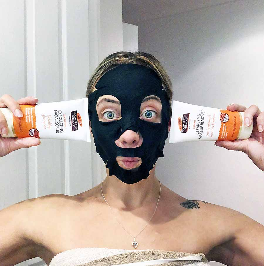 Jess Neill with a charcoal face mask on, pulling a face and showing the face wash products from Palmers