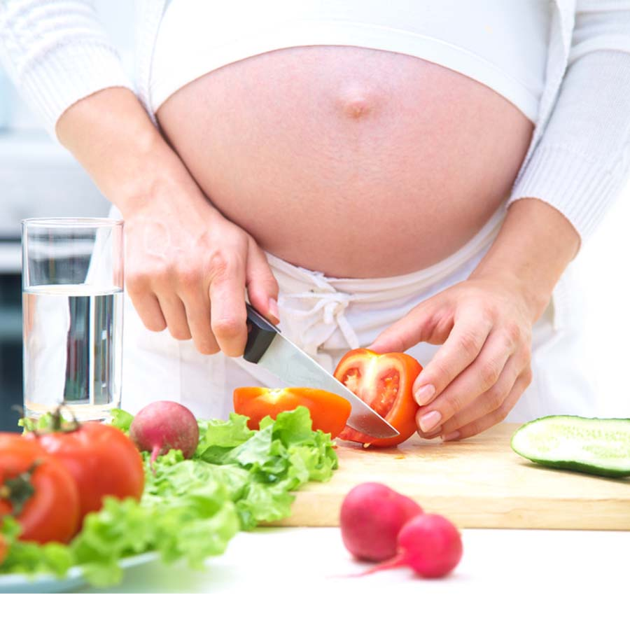 pregnant lady cutting up a tomato, surrounded by vegetables and fruits