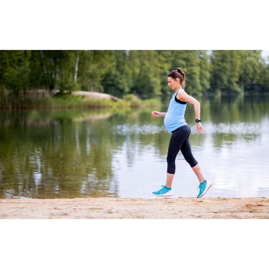 Pregnant woman running along a beautiful lake