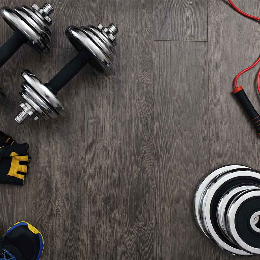 A flat lay of dumbbells, running shoes, weight plates and skipping rope