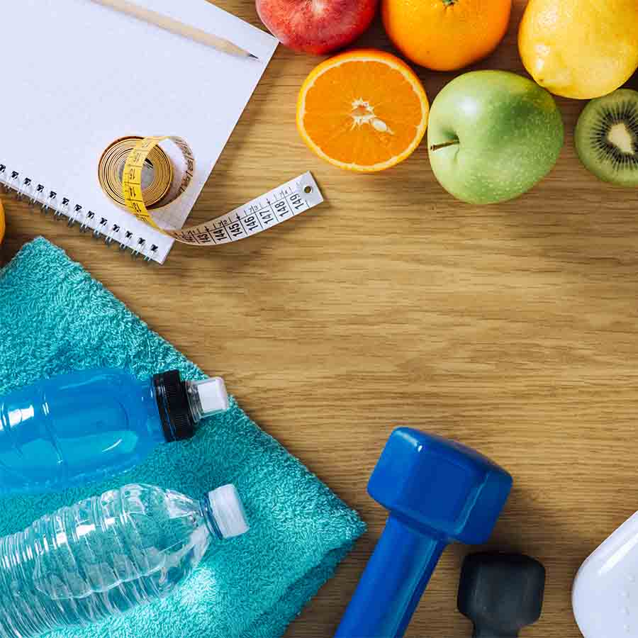 A layout of a water bottle, blue dumbbell, tape measure, writing pad and various fruits on a light wooden surface