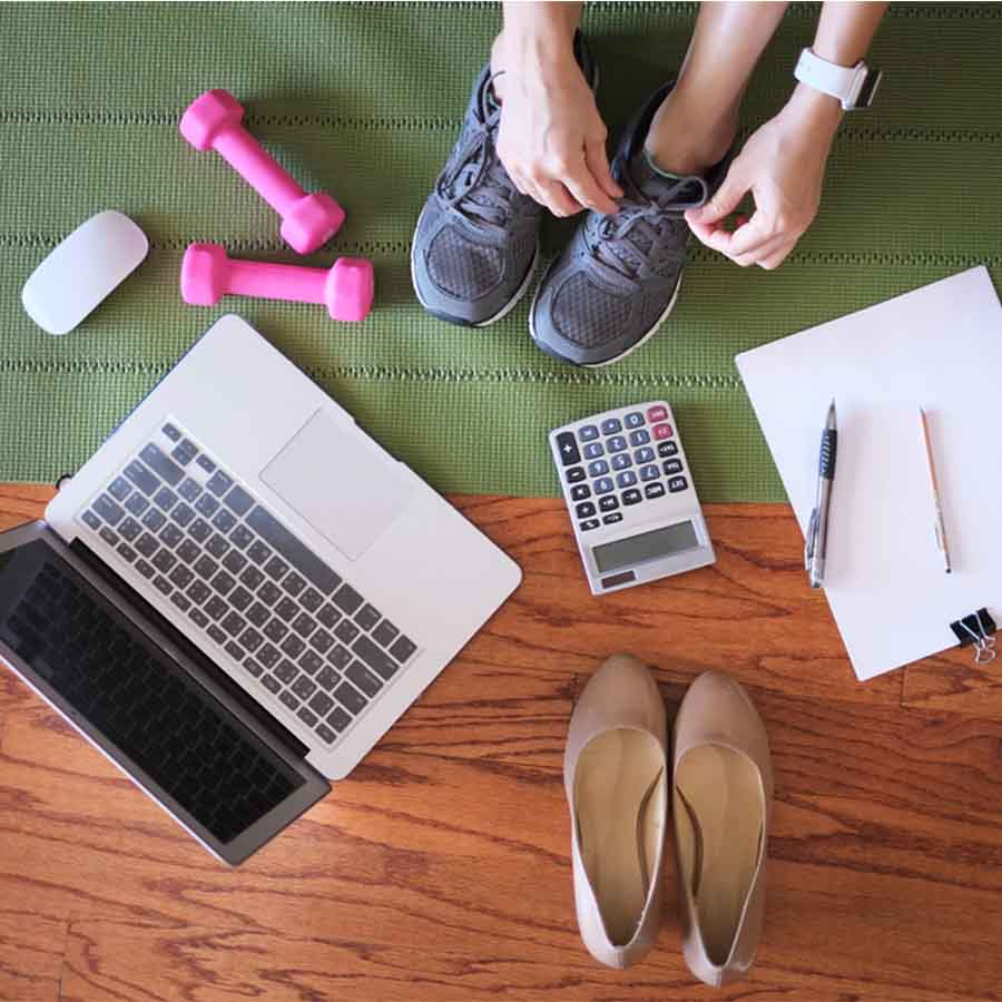 A flatlay including shoes, running shoes, laptop, paper and pens, calculator, and pink small dumbbells