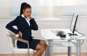 A lady sitting at an office desk with a computer, grabbing her neck and lower back and wincing in pain