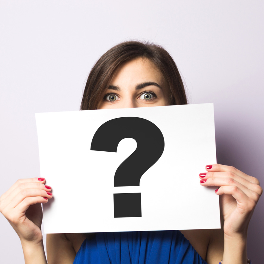 A woman holding a question mark in front of her face with wide eyes