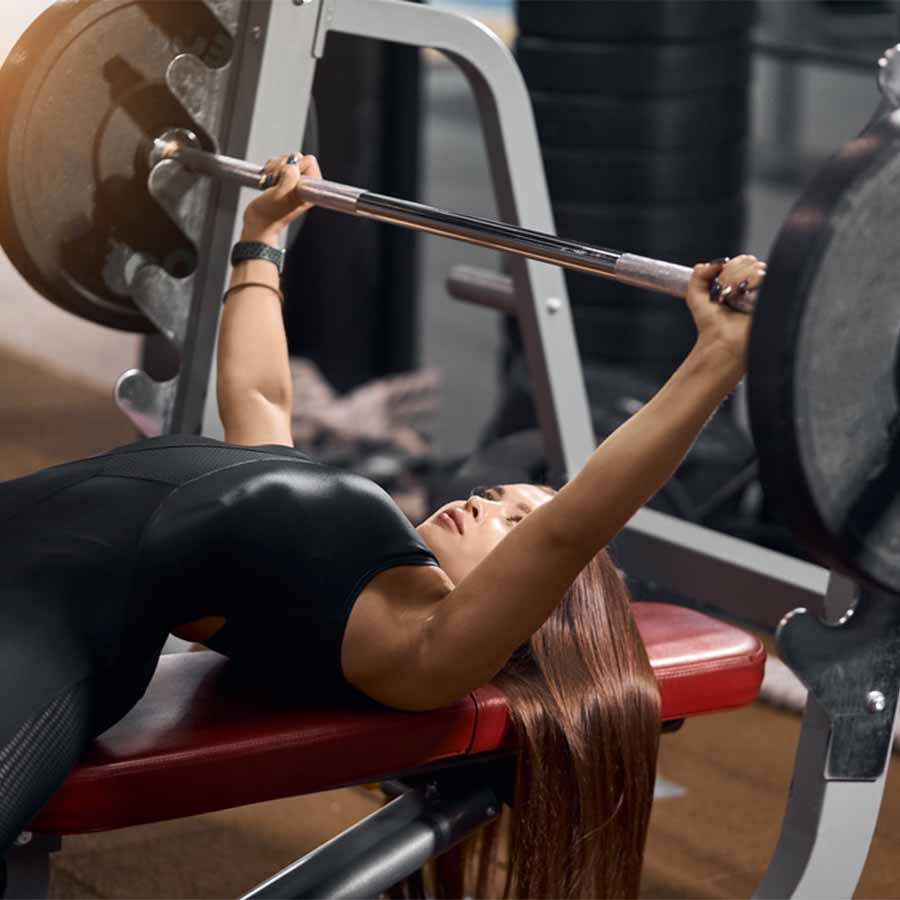 A woman on a red bench performing a bench press
