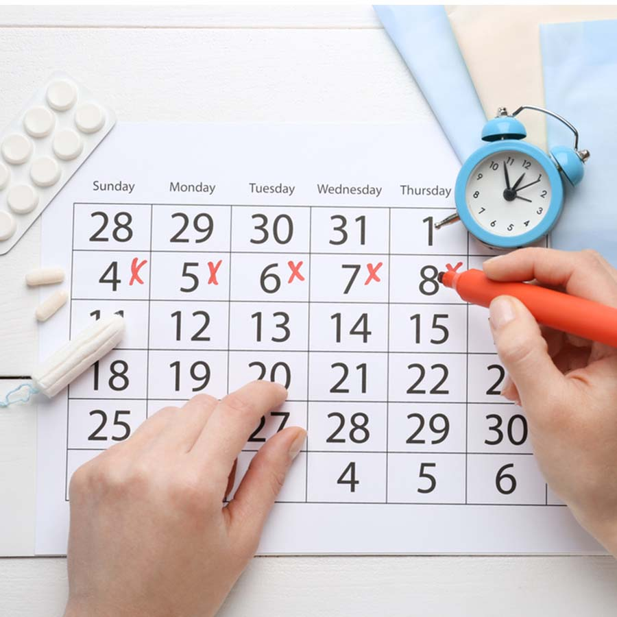 A woman writing on a calendar with a clock next to her hand, laid out on a white wooden desk