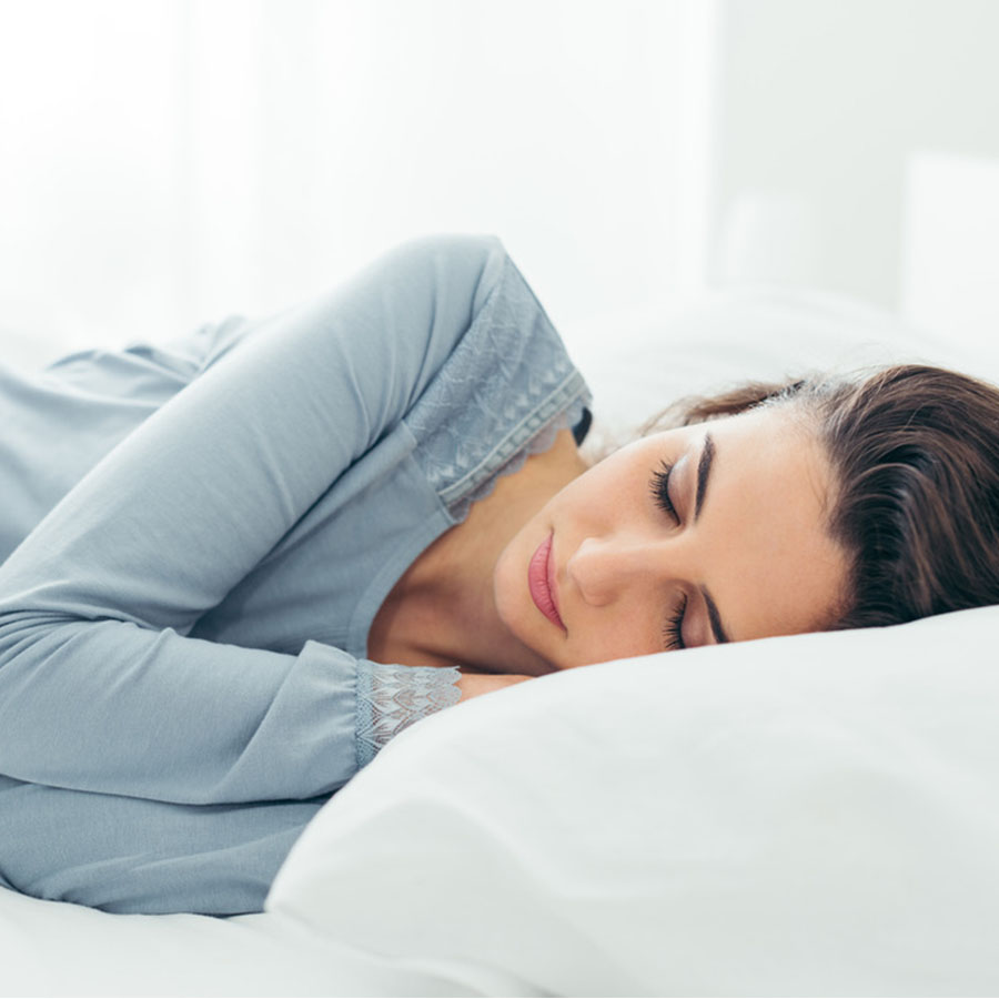A woman in a white bed sleeping on her side with her hands tucked under her head