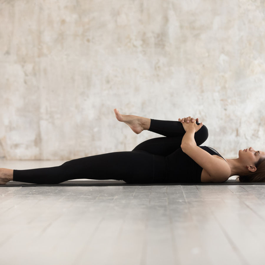 a woman in a plain room, layi9ng on her back stretching one leg