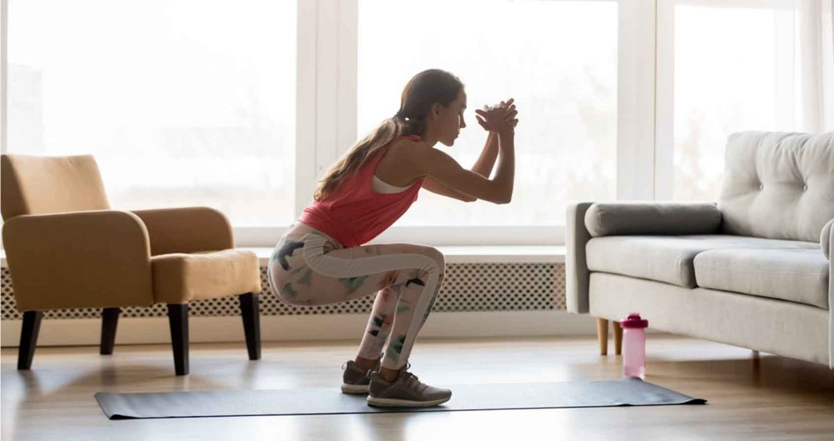 a girl in a well lit living room performing a bodyweight squat