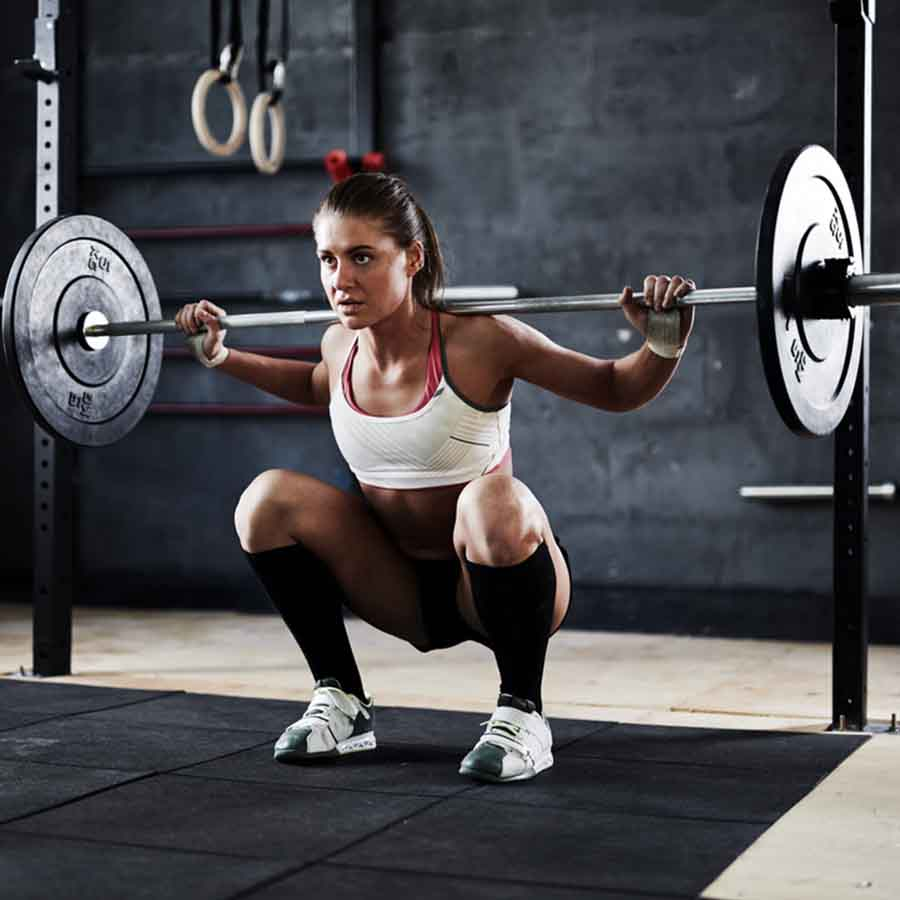 A woman in a dark gym squatting with a barbell on her back.