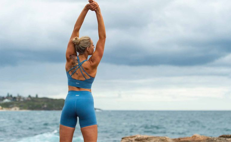 Jess standing in front of the water at the beach, stretching her arms and looking out at the ocean, with her back to the camera in a light blue activewear outfit,