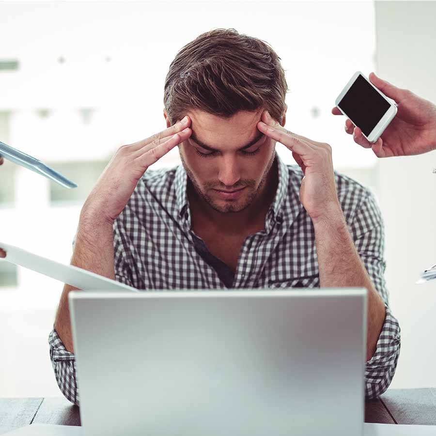 A man sitting at a desk in front of a computer with his head in his hands, visibly stressed while people's hands around him hold out papers and phones and pencils