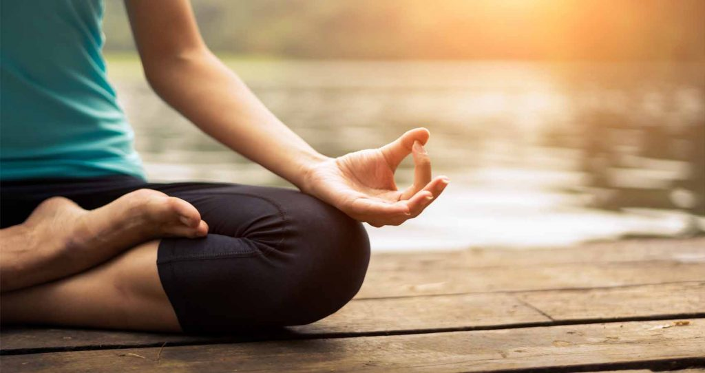 A woman's legs and hand seen in a meditation pose on a wooden by the water dock at sunset