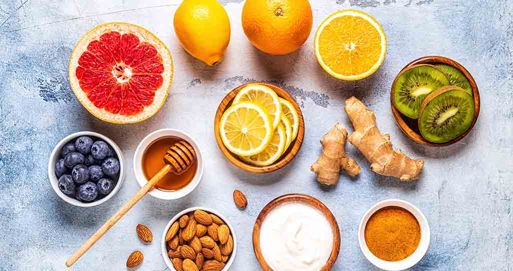 A flatlay on a white and light blue backdrop. It includes ginger, oranges, grapefruits, honey, almonds and other foods high in vitamin C or known for fighting the flu.