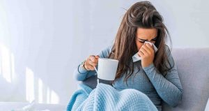 a woman sitting in bed, covered in a blue blanket wearing a jumper. She is holding a mug and sneezing into a tissue.