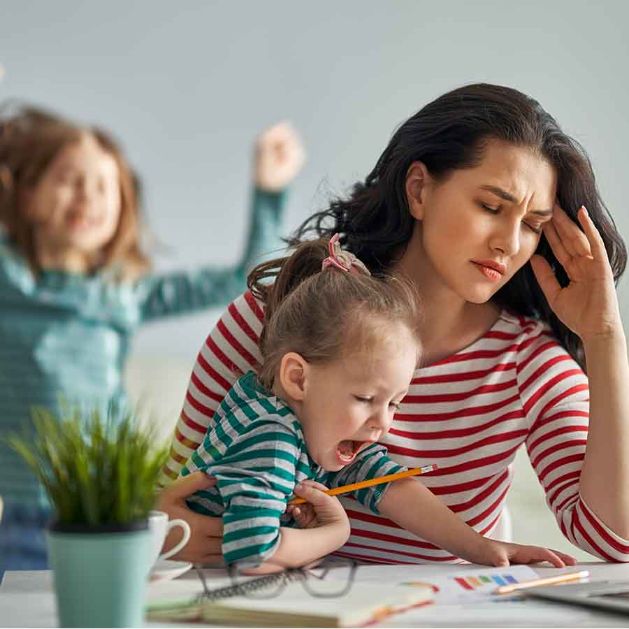 An image of a young mother sitting at a desk, looking stressed while trying to get work done, while her young child crawls on her lap and an older child dances wildly in the background.
